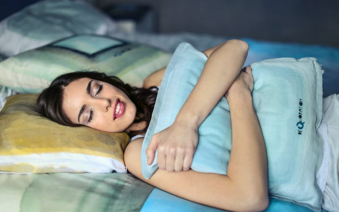 woman-bed-hugging-a-blue-pillow